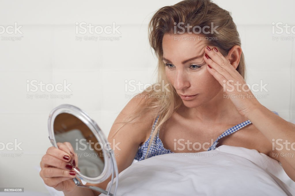 Woman looking in the mirror at her facial wrinkles stock photo