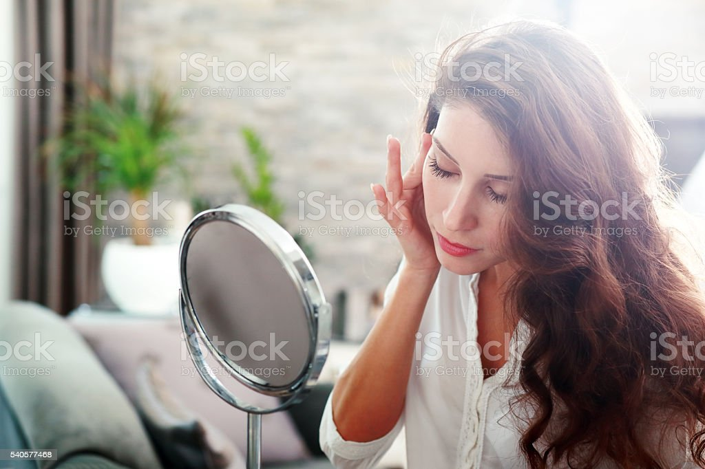 woman looking in the mirror stock photo