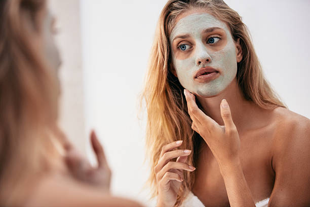 Woman looking in the mirror with face mask - Photo