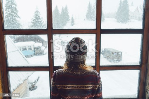 Young Caucasian woman  looking in the window in  winter