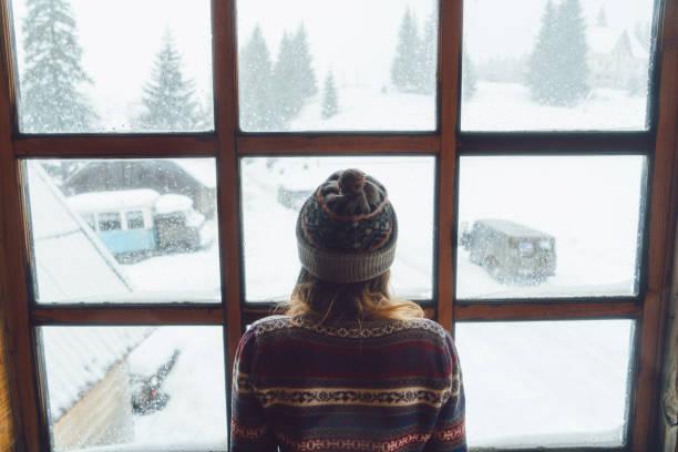 frau im fenster im winter - kaltes wetter stock-fotos und bilder