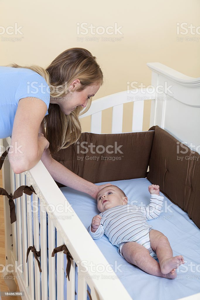 XXXL. Young mother looking into baby crib where her baby boy is lying.