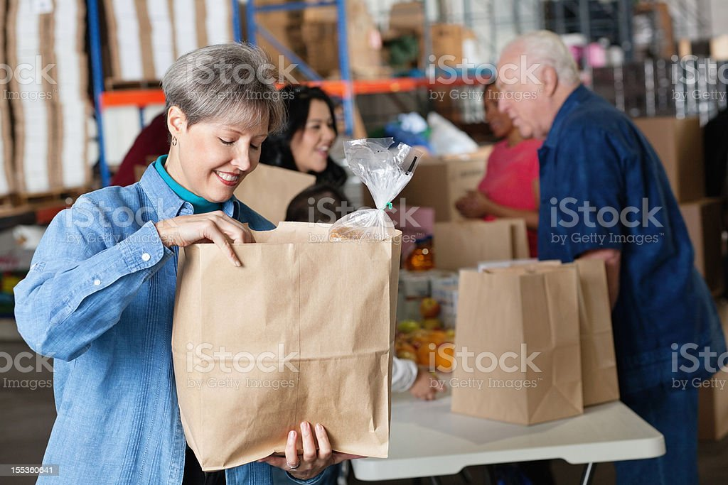 Woman looking into her donated groceries bag at donation facility royalty-free stock photo