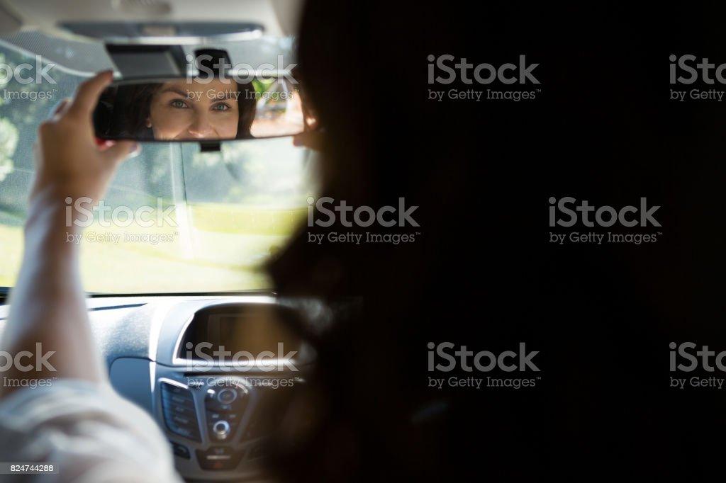 Olhando no espelho retrovisor enquanto dirigia um carro de mulher - foto de acervo