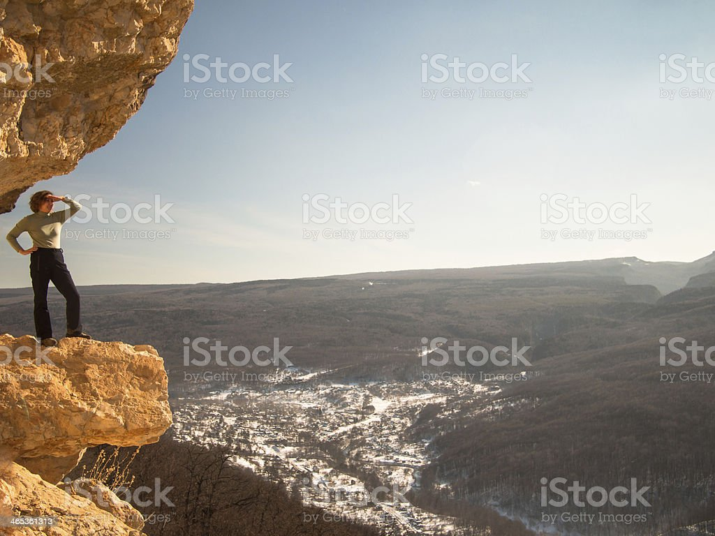 Woman looking into the distance while standing on a ledge stock photo
