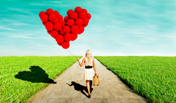 woman looking love while walking with heart shaped red balloons and a suitcase - donna valigia solitudine foto e immagini stock