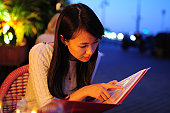 Young  woman is looking menu at restaurant