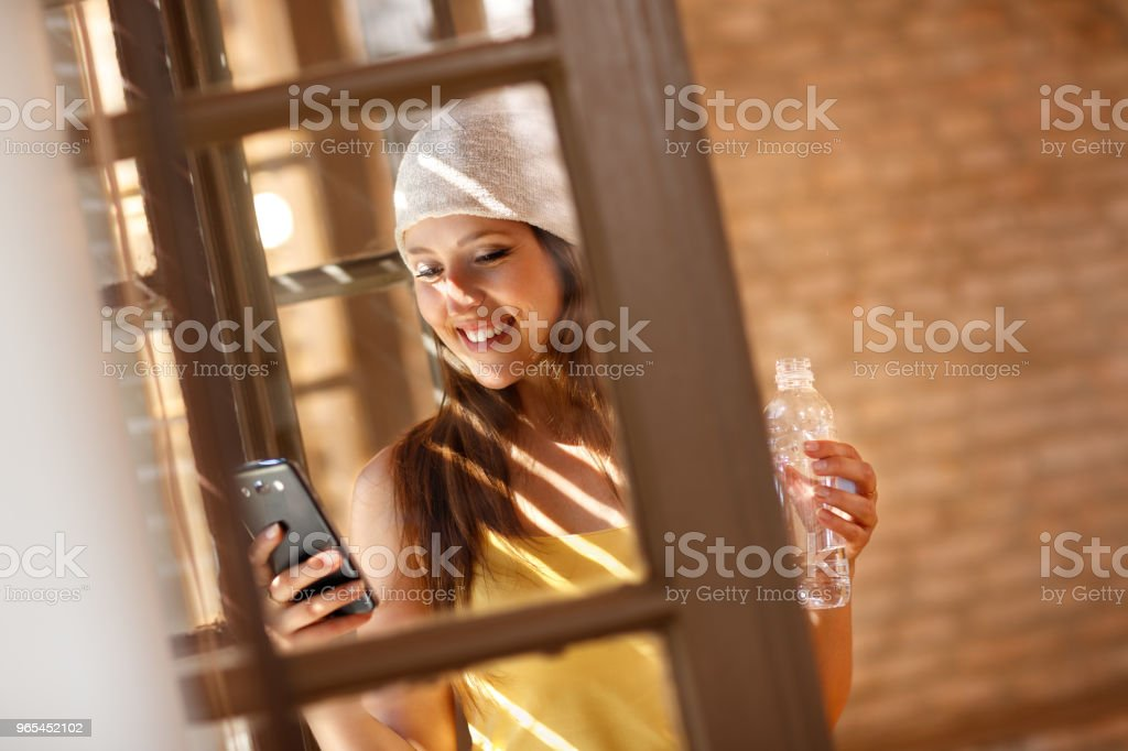 Woman looking on cell phone by window royalty-free stock photo