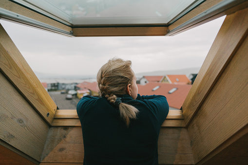 istock Woman looking our of the window on city 1135544729