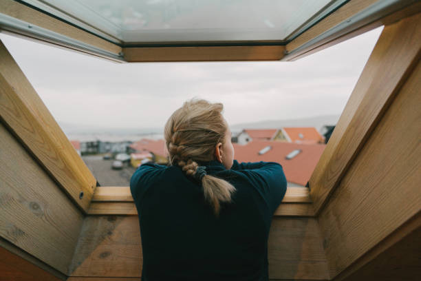 Woman looking our of the window on city stock photo