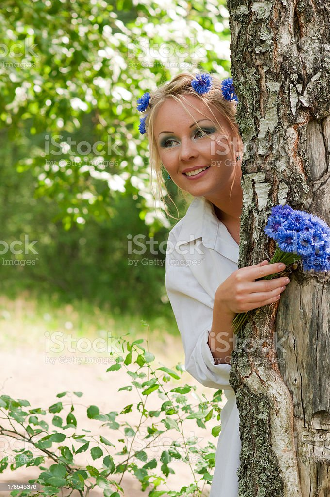 Woman looking out from behind a tree royalty-free stock photo