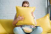 ポップコーンを家でホラー映画を見ている間クッションから探している女性