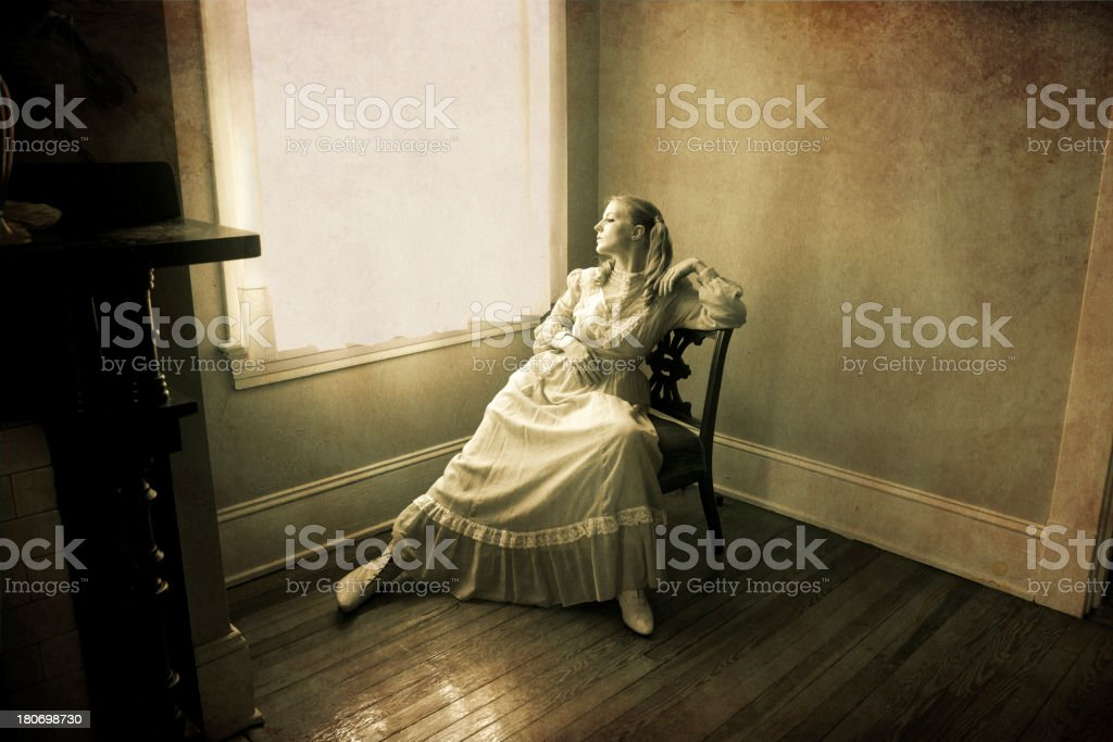 Woman Looking out of a Window stock photo