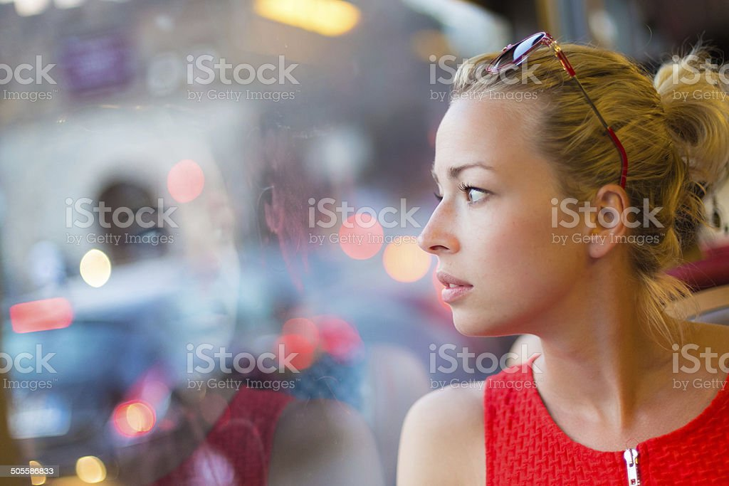 Woman looking out tram's window. stock photo