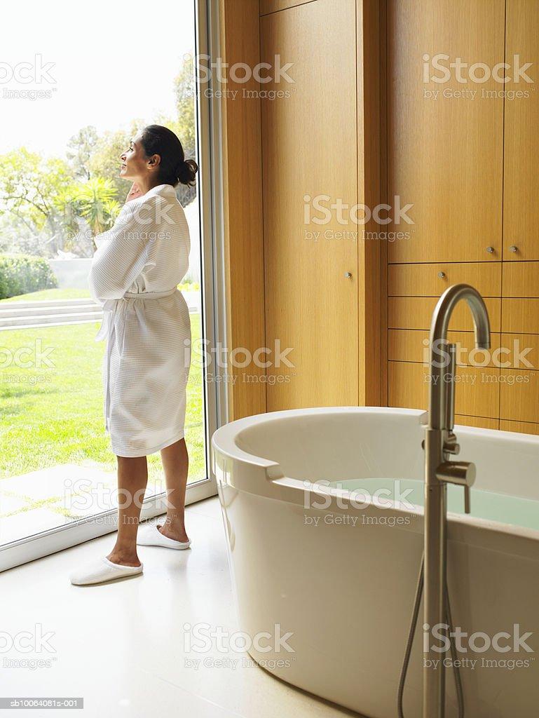 Mujer mirando por la ventana en el baño foto de stock libre de derechos
