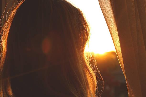Mujer mirando por la ventana - foto de stock