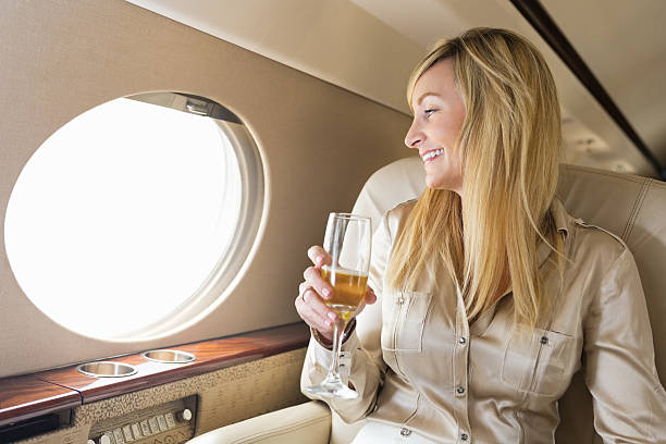 Woman looking out window while drinking champagne on private jet stock photo