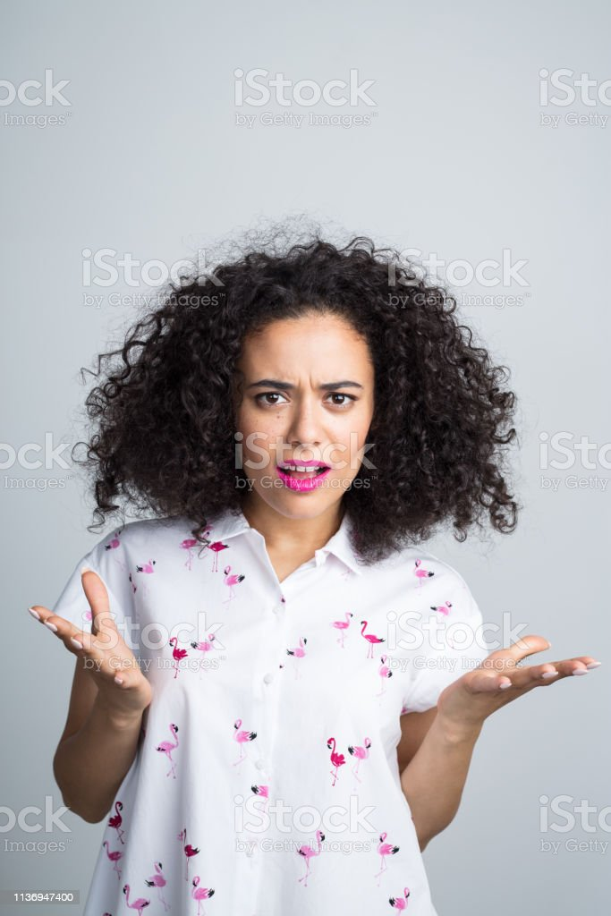 Woman looking really annoyed Portrait of curly haired young woman looking annoyed against gray background 20-24 Years Stock Photo