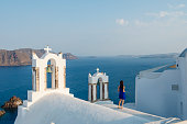 Woman looks at seascape from the roofs of the Greek village