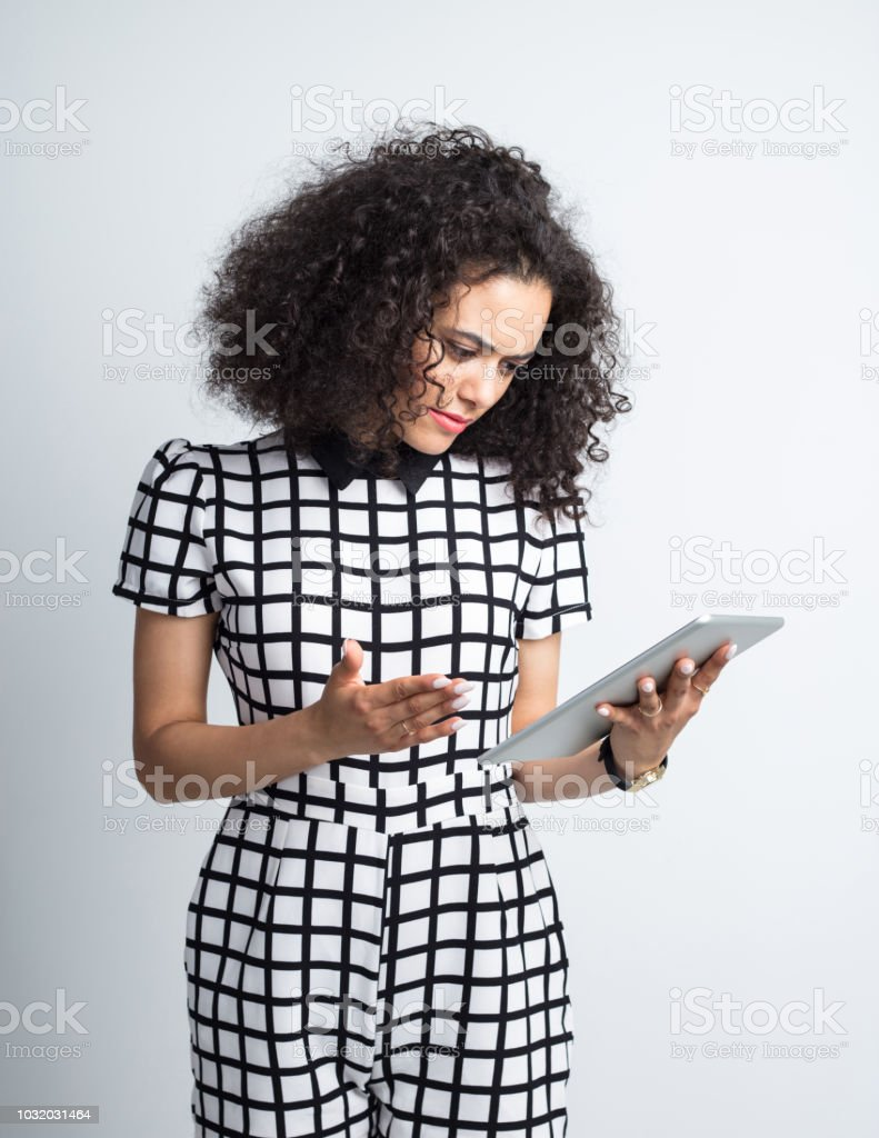 Woman looking seriously at digital tablet Young woman in casual outfit looking at digital tablet seriously against gray background 20-24 Years Stock Photo