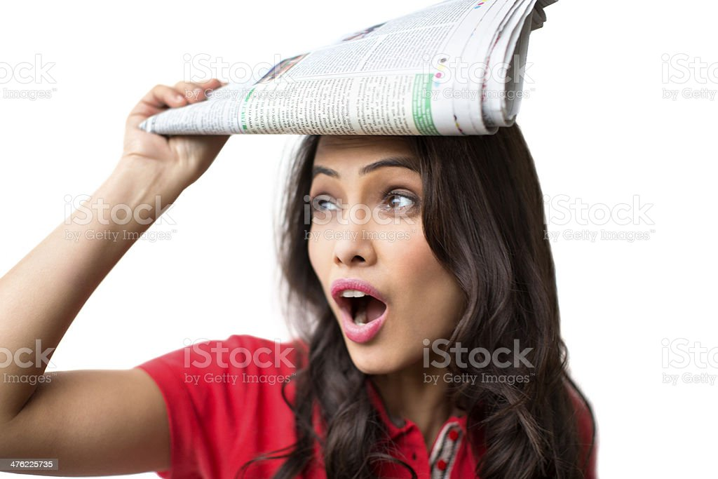 woman looking shocked with holding a newspaper royalty-free stock photo