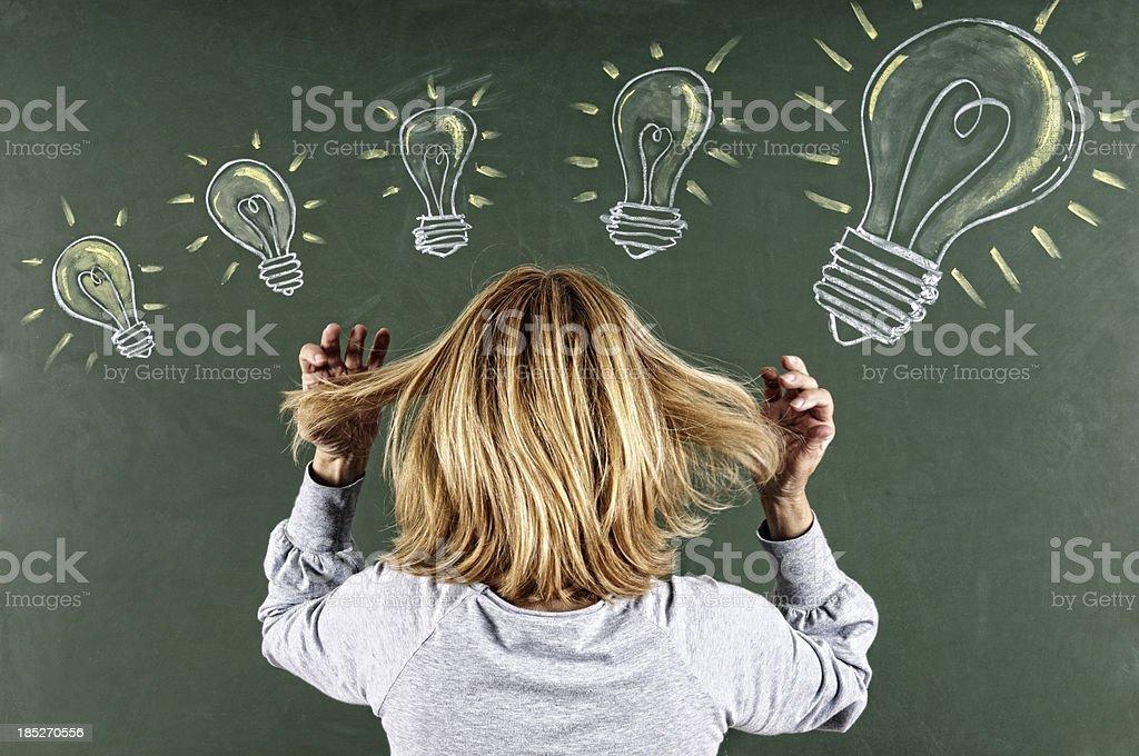 Woman Looking Sketched Light Bulbs on Blackboard royalty-free stock photo