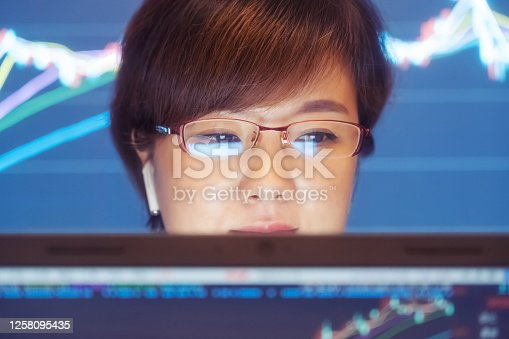 850852928 istock photo Woman looking stock market Data on computer 1258095435