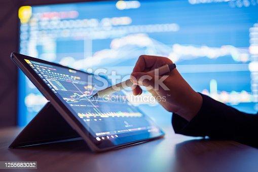istock Woman looking stock market Data on smart phone 1255683032