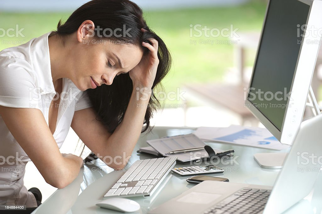 Woman looking stressed at her desk royalty-free stock photo