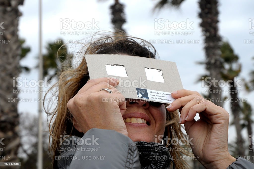 woman looking the solar eclipse with filtered glasses stock photo