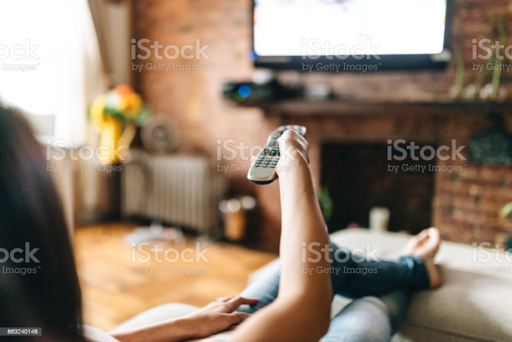 woman looking the tv at home - Foto stock royalty-free di Abbigliamento casual