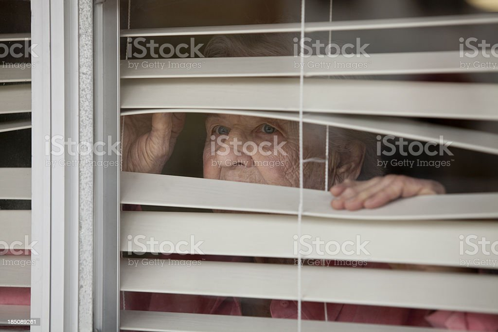 Woman looking throgh blinds royalty-free stock photo