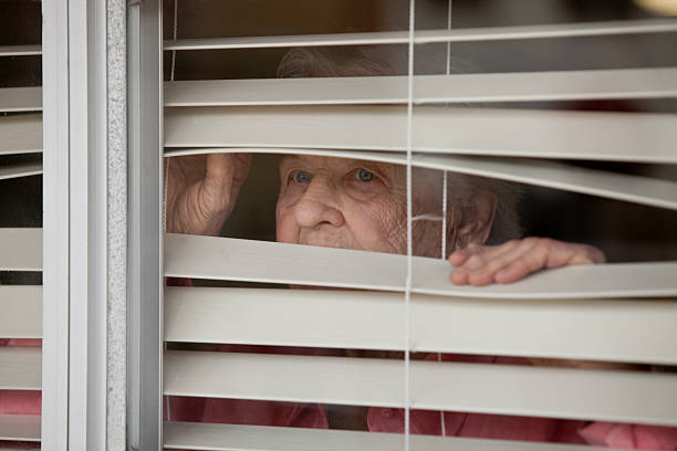 Woman looking throgh blinds stock photo