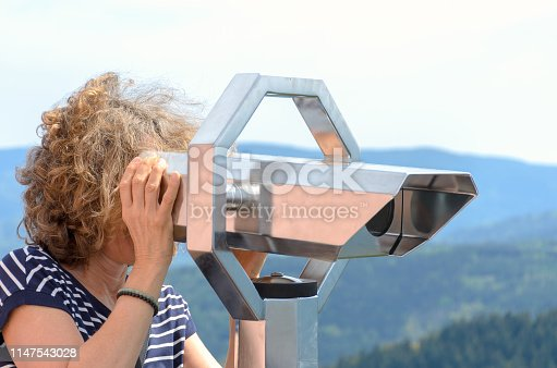 Woman tourist looking through a binocular telescope from a vantage point in mountainous terrain