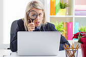 istock Woman looking through a magnifying glass in front of computer 518297149