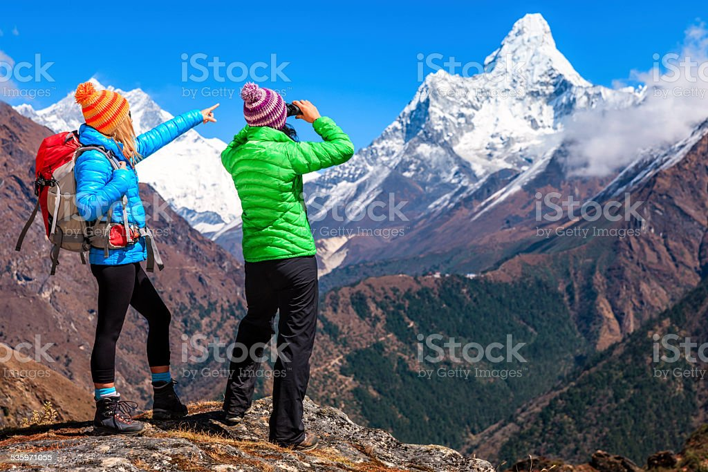 Woman looking through binoculars at Ama Dablam, Mount Everest Region stock photo