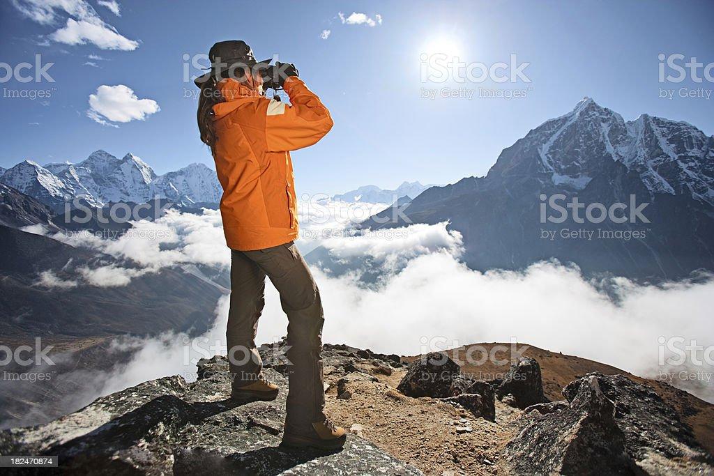 Woman looking through binoculars at Taboche in Sagarmatha National Park stock photo