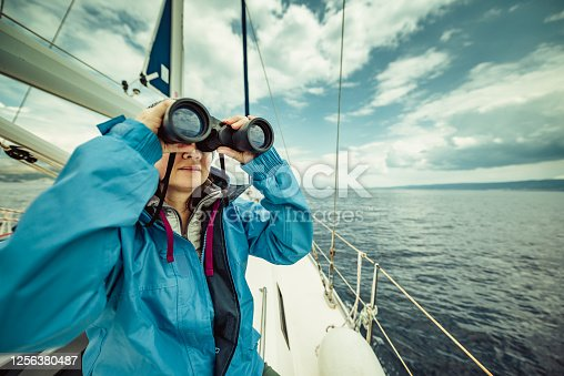 A woman on the sailing yacht looking through binoculars