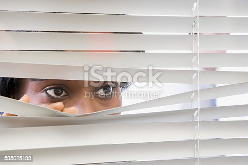 istock Woman looking through blinds 535025133