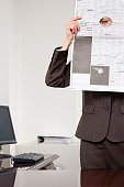 istock Woman looking through hole in newspaper 532606109