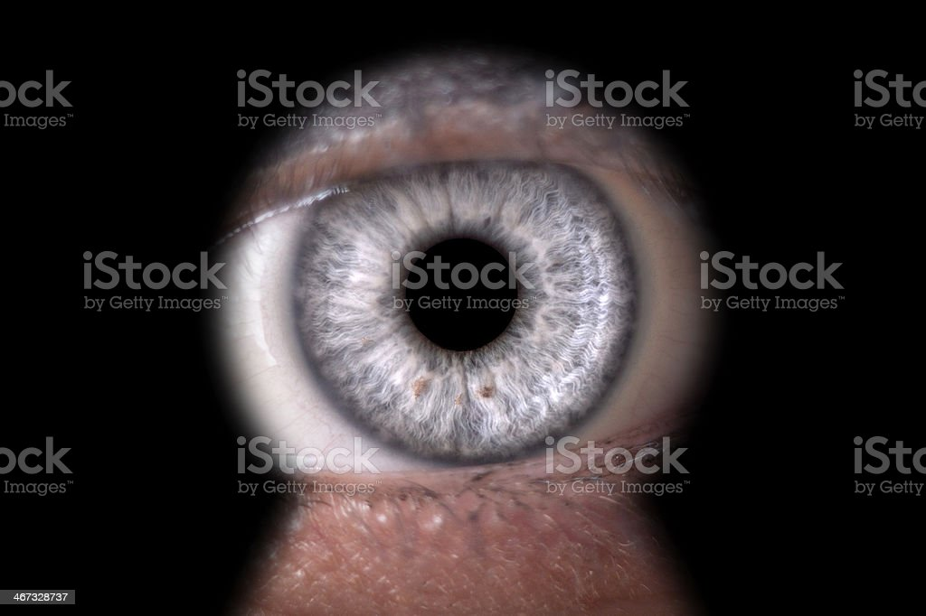 woman looking through keyhole stock photo