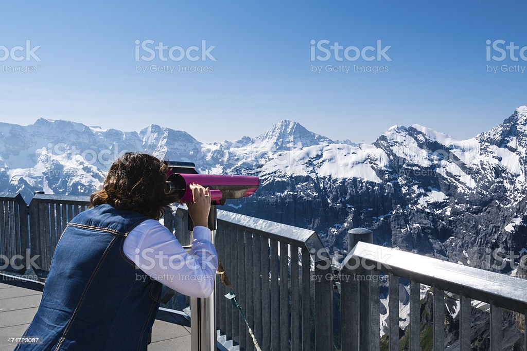 Woman looking through large binoculars observing snow cove royalty-free stock photo