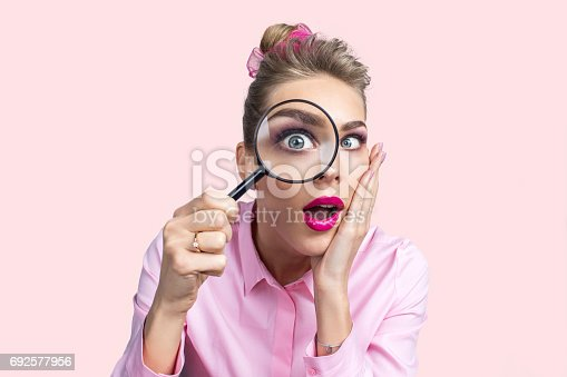 istock Woman looking through magnifying glass 692577956