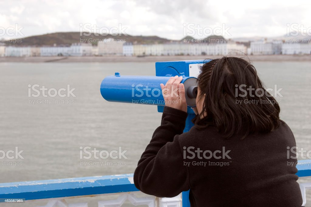 Woman looking through telescope stock photo