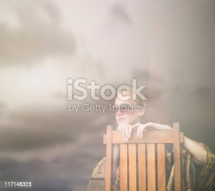 istock Woman looking through the window at sunset 117148323
