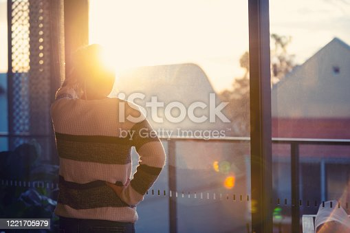 917874758 istock photo Woman looking through the window at sunset. 1221705979