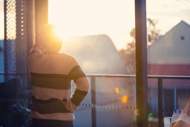 Frau schaut bei Sonnenuntergang durch das Fenster. – Foto