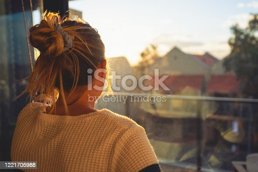 917874758 istock photo Woman looking through the window at sunset. 1221705988