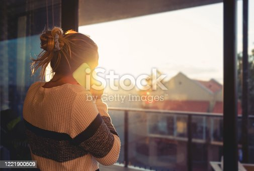 Woman looking through the window at sunset. She is alone and looks a little sad or depressed. She is talking on her mobile phone.