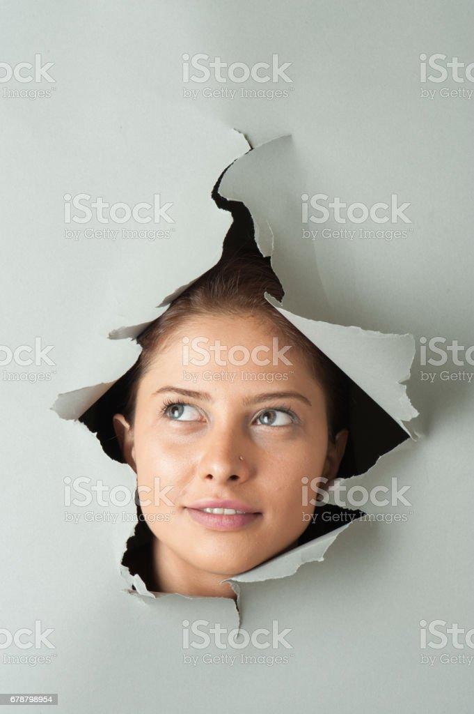Femme à la recherche par le biais de papier Déchiré photo libre de droits